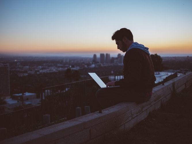 Photograph of a man sat on a wall using a laptop in the evening